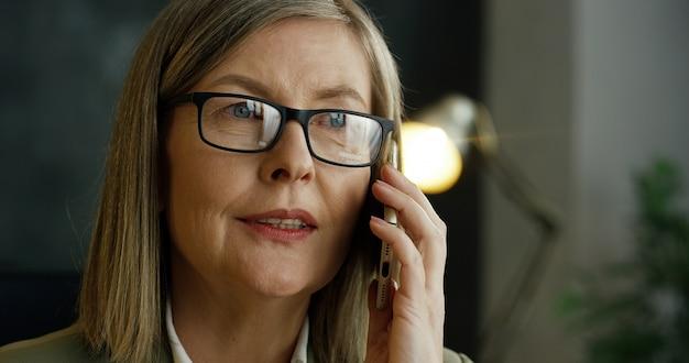 Sluit omhoog van hogere knappe vrouw in glazen sprekend op mobiele telefoon over zaken in haar bureau.