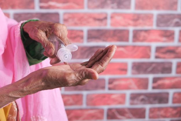 Sluit omhoog van hogere vrouwenhand die ontsmettingsgel gebruikt om virus te verhinderen.