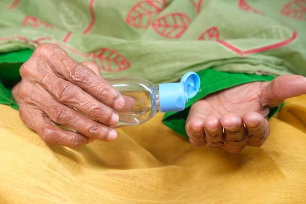 Sluit omhoog van hogere vrouwenhand die ontsmettingsgel gebruikt om virus te verhinderen