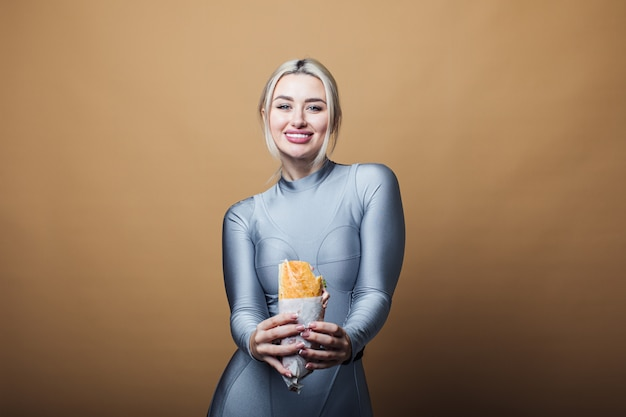 Sluit omhoog van hongerige vrouw met glimlach, houdend en etend grote sandwich. concept van fast food