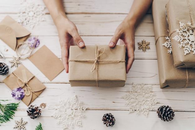 Sluit omhoog van huidig de giftvakje van de handenvrouw op houten lijst met kerstmisdecoratie.