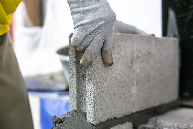 Sluit omhoog van industriële metselaar die bakstenen installeren op bouwwerf, die muren bouwen.