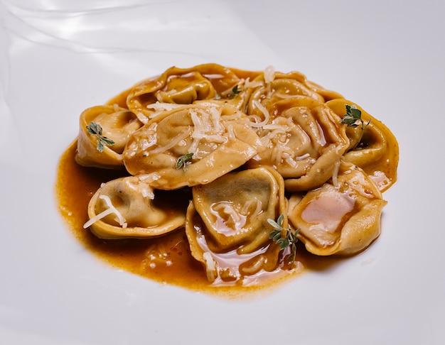 Sluit omhoog van italiaanse boldeegwaren in saus die met parmezaanse kaas wordt versierd