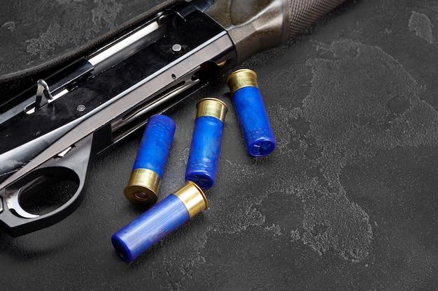 Sluit omhoog van jachtgeweer en patronen op donkergrijze achtergrond