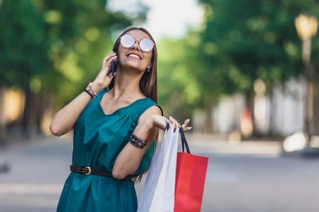 Sluit omhoog van jong charmant donkerharig kaukasisch wijfje met het winkelen zakken die met tanden glimlachen en op telefoon spreken