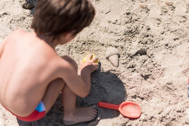 Sluit omhoog van jong geitje het spelen met zand bij het strand
