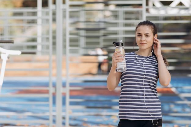 Sluit omhoog van jong gezond wijfje die oefeningskleding dragen kijkend vermoeid na oefening en holdingsschudbeker in haar hand