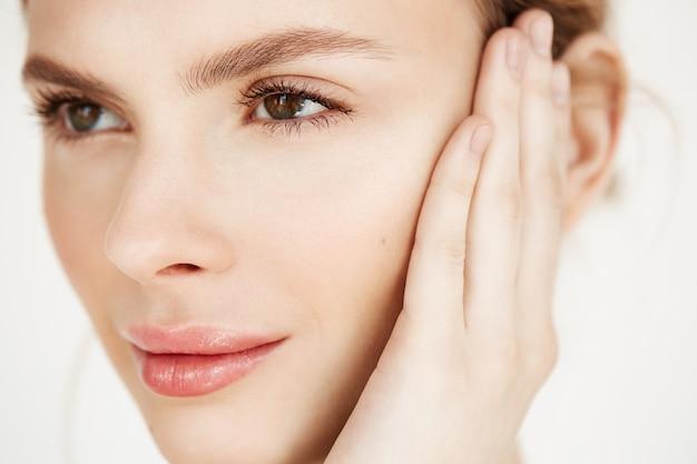 Sluit omhoog van jong mooi meisje glimlachend wat betreft gezicht. spa schoonheid gezondheid en cosmetologie concept.