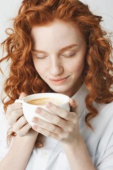 Sluit omhoog van jong teder roodharigemeisje die met gesloten ogen holdingskop van koffie glimlachen.