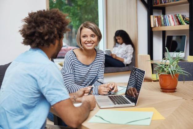 Sluit omhoog van jong vrolijk studentenmeisje met licht haar in de zitting van het loodjeskapsel op vergadering met vriend van universiteit, doend teamproject, zoekend naar informatie over laptop.