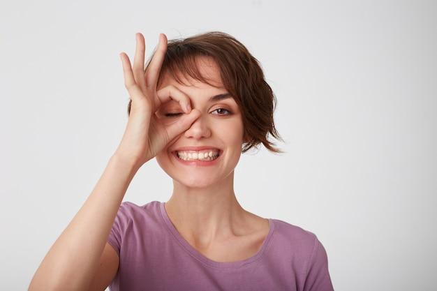 Sluit omhoog van jonge aantrekkelijke gelukkige kortharige dame in leeg t-shirt, die zich over witte muur bevindt en door ok gebaar kijkt en in het algemeen positief emotieconcept glimlacht.