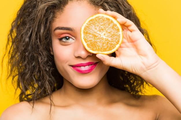 Sluit omhoog van jonge afrikaanse amerikaanse mooi en maak omhoog vrouw die een grapefruit houden