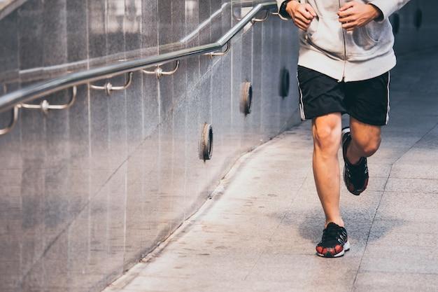 Sluit omhoog van jonge atletische mensenjogging op stadsbrug bij de ochtend.