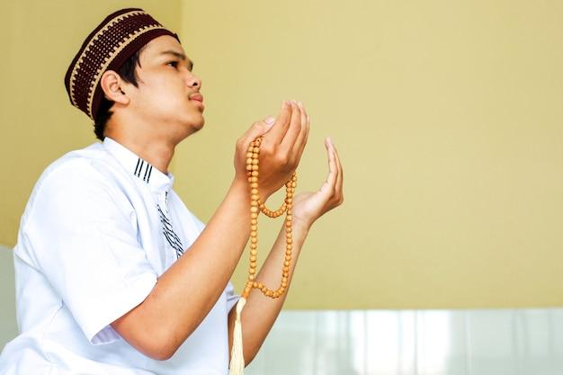Sluit omhoog van jonge aziatische moslim die tot god bidt