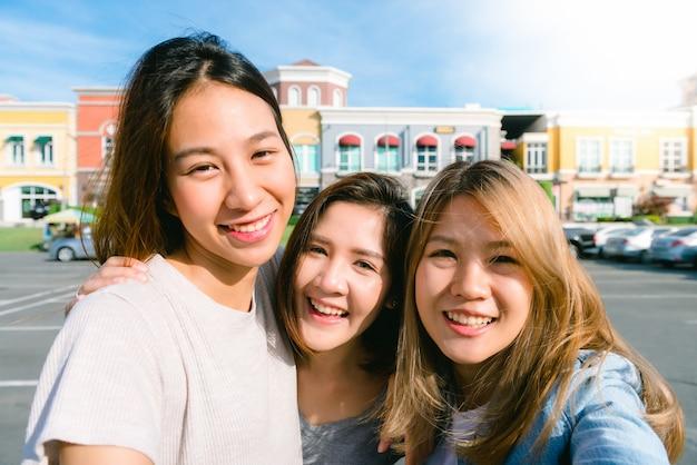 Sluit omhoog van jonge aziatische vrouwengroep selfie zelf in de stad van pastelkleurgebouwen