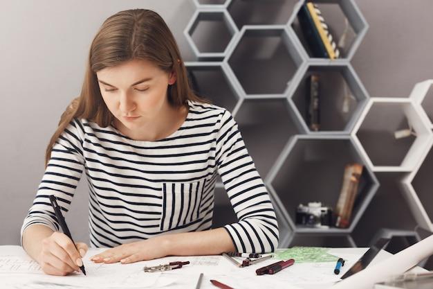 Sluit omhoog van jonge geconcentreerde mooie jonge ontwerperzitting bij lijst in lichte ruimte, doend voor blauwdrukken gebruikend pen en heerser. bedrijfsconcept