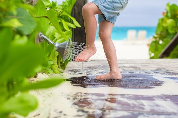 Sluit omhoog van jonge geitjesbenen onder een stranddouche