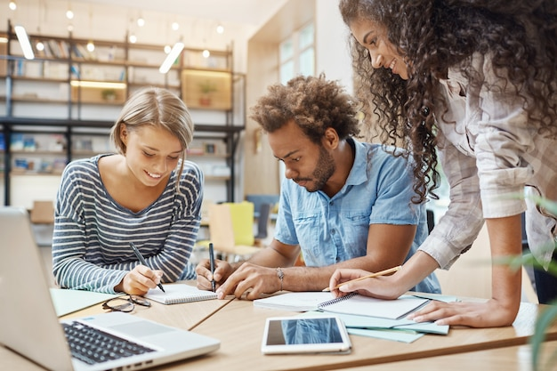 Sluit omhoog van jonge groep startapers die in bibliotheek zitten die onderzoek naar toekomstig temproject maken, kijkend door grafiek op laptop, die nieuwe ideeën schrijven. bedrijfs, teamworkconcept