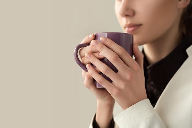 Sluit omhoog van jonge mooie vrouwenhanden die hete kop van koffie of thee houden. ochtendkoffie, koud seizoen, koffiepauze op kantoor of koffieliefhebber concept.