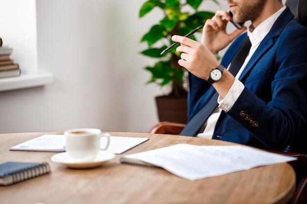 Sluit omhoog van jonge succesvolle zakenman die op telefoon spreekt.