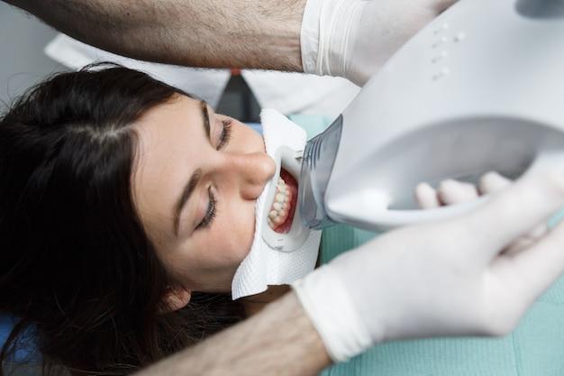 Sluit omhoog van jonge vrouw die een tanden ontvangen die behandeling witten bij een tandarts.