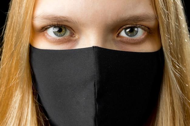 Sluit omhoog van jonge vrouw die zwart gezichtsmasker draagt. pandemisch coronavirus covid-19 quarantaineperiode concept.