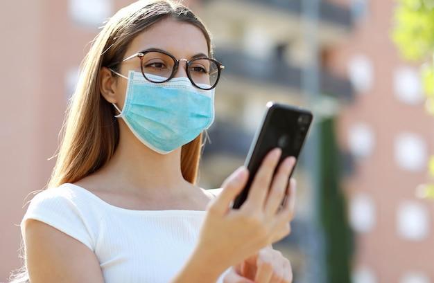 Sluit omhoog van jonge vrouw met het medische masker typen op slimme telefoon in stadsstraat.