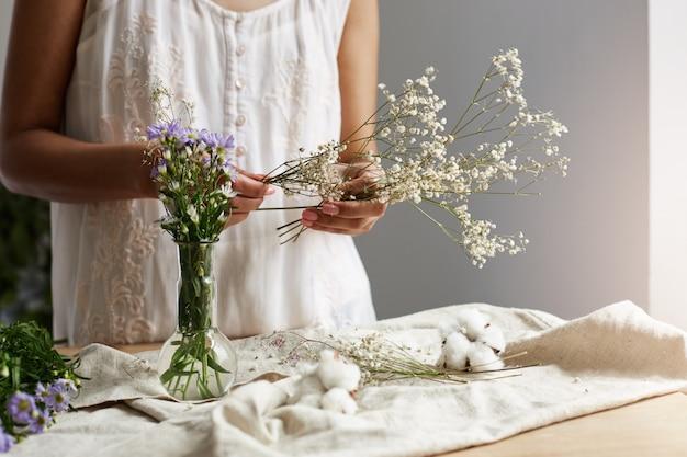 Sluit omhoog van jonge vrouwelijke bloemist die met bos van bloemen op het werk werken.
