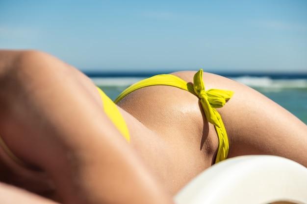 Sluit omhoog van jonge vrouwenheup en schouder die op strandstoel op overzeese kust zonnebaden.
