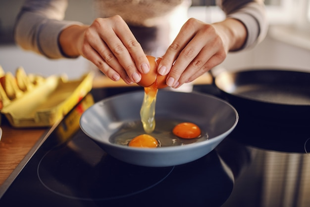 Sluit omhoog van kaukasisch vrouwen brekend ei en makend zonnige kant omhoog eieren. binnenlandse keuken interieur. ontbijt voorbereiding.