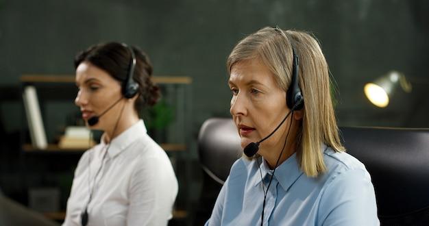 Sluit omhoog van kaukasische hogere vrouw in hoofdtelefoon werkend in bureau van call centre. service voor klanten concept.