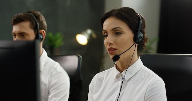 Sluit omhoog van kaukasische mooie vrouw die in hoofdtelefoon met klant bij computer babbelen en probleem oplossen.