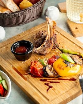 Sluit omhoog van kebab van lamsribben die met gerookte groenten en saus worden gediend