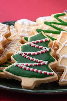 Sluit omhoog van kerstmis verfraaide suiker cooikes in een plaat op rode lijstachtergrond.