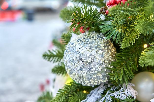 Sluit omhoog van kerstmisboom die met silferr fonkelende ballen en slinger wordt verfraaid met lichten.