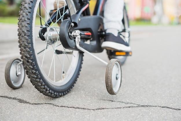 Sluit omhoog van kind berijdende fiets buiten
