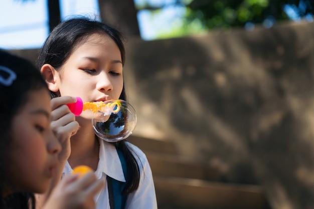 Sluit omhoog van kind blazende zeepbels en hebbend pret in de zomerpark in openlucht