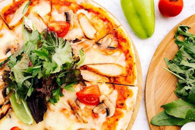 Sluit omhoog van kippenpizza met paddestoeltomaat die met kruiden wordt bedekt