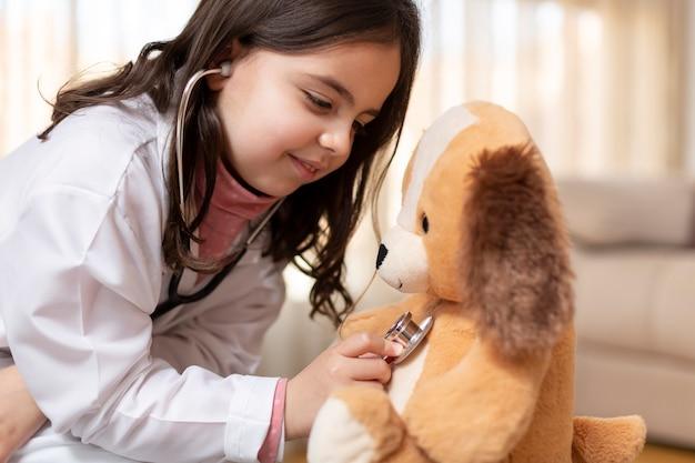 Sluit omhoog van klein kind kleedde zich als arts die haar teddybeer auscultating