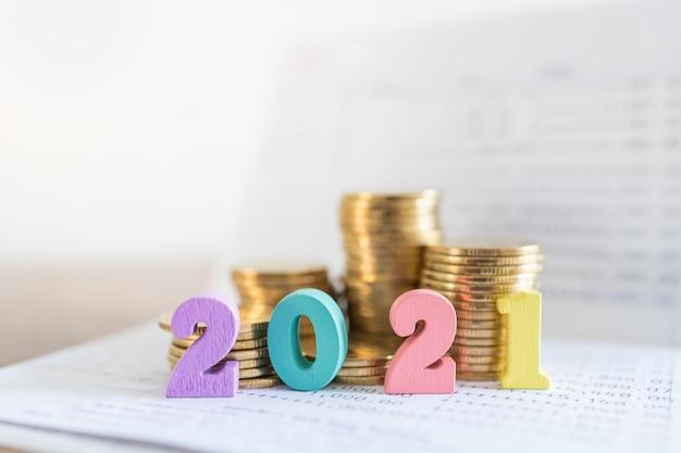 Sluit omhoog van kleurrijk houten aantal op bankbankboekje met stapel gouden muntstukken met exemplaarruimte.