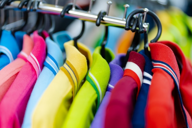 Sluit omhoog van kleurrijk polooverhemd op hangers