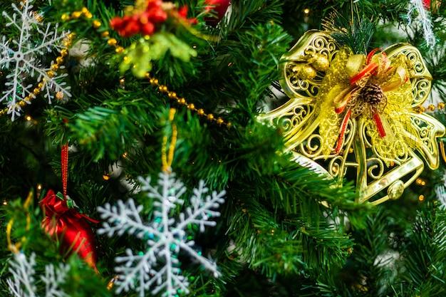 Sluit omhoog van kleurrijke ballen op groene kerstboom, decoratie tijdens kerstmis en nieuwjaar.