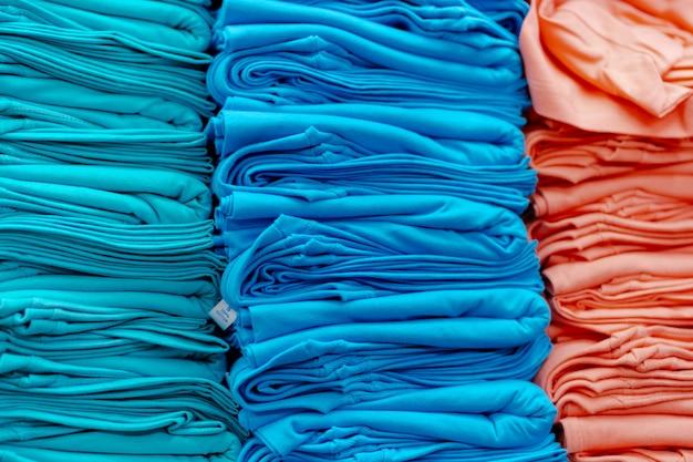 Sluit omhoog van kleurrijke die t-shirts op planken worden gestapeld