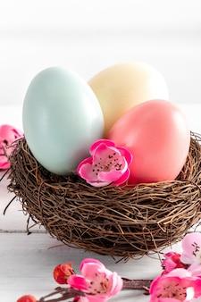 Sluit omhoog van kleurrijke paaseieren in het nest met roze pruimbloem op heldere witte houten lijstachtergrond.
