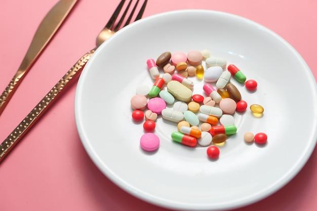 Sluit omhoog van kleurrijke pillen op plaat.