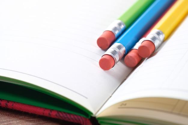 Sluit omhoog van kleurrijke potloden op blocnote