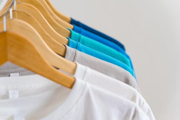 Sluit omhoog van kleurrijke t-shirts op hangers, kleding