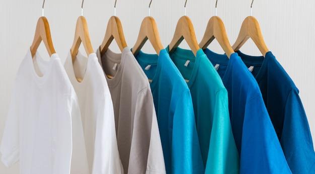 Sluit omhoog van kleurrijke t-shirts op hangers, kledingsachtergrond