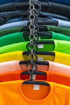 Sluit omhoog van kleurrijke t-shirts op hangers