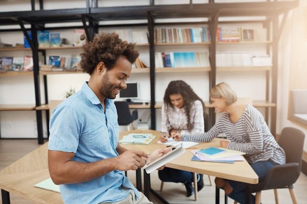 Sluit omhoog van knappe jonge donkerhuidige perspectiefondernemer kijkend in digitale tablet zoekend informatie over teamproject. vriend op bijeenkomst in de bibliotheek